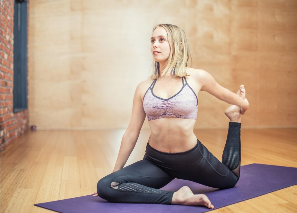 Woman in athletic clothes doing yoga pose on purple yoga mat